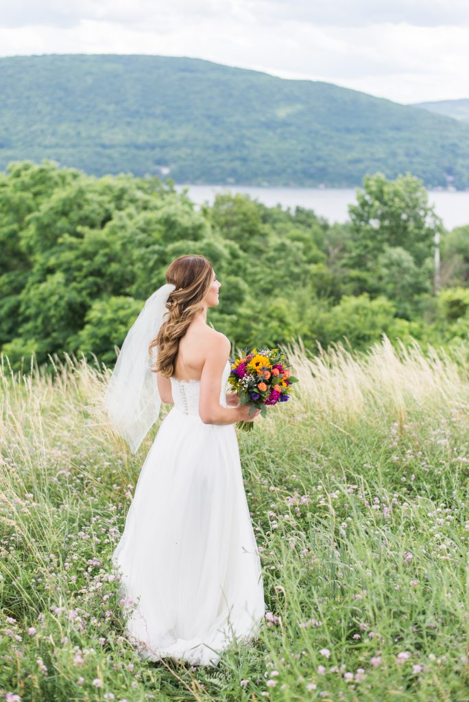 wildflower wedding inspiration, boho wedding inspiration, boho bride photos, sunflower wedding inspiration, bright wedding flowers, gorgeous wedding dress, white wedding dress, fingertip veil, indie wedding ideas, finger lakes wedding photos, finger lakes wedding ideas, vineyard wedding, bristol harbour wedding, wedding at bristol harbour, wedding photos on a lake, bridal portraits, low back wedding dress, half up half down hair do, half up half down wedding hair